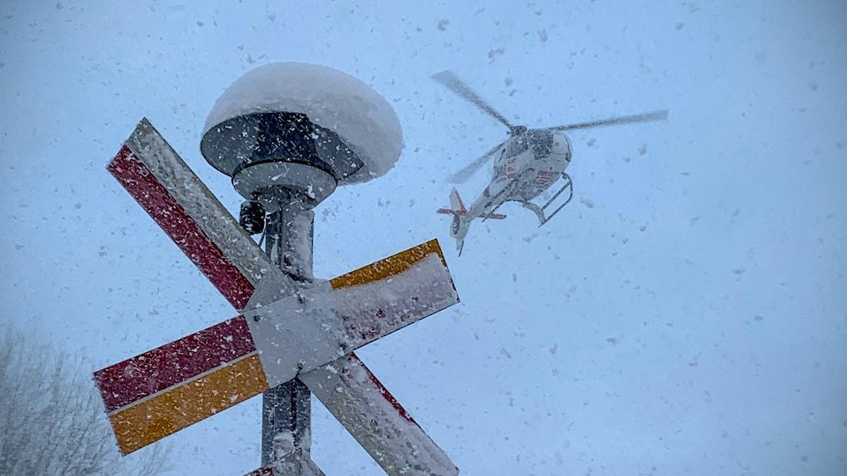 En helikopter flyger ovanför en tågräls.