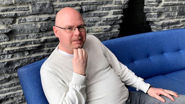 man i ljus tröja och glasögon sitter i blå soffa