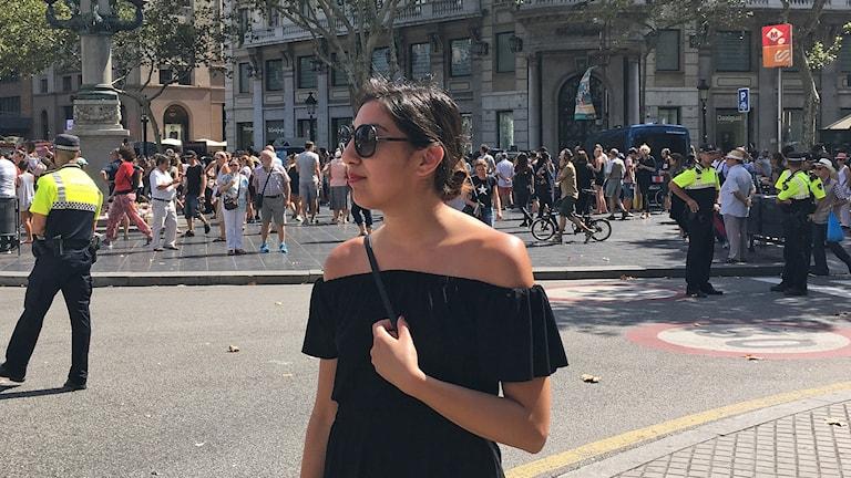 Mörkhårig ung kvinna står vid en folkrik gata i Barcelona med patrullerande poliser