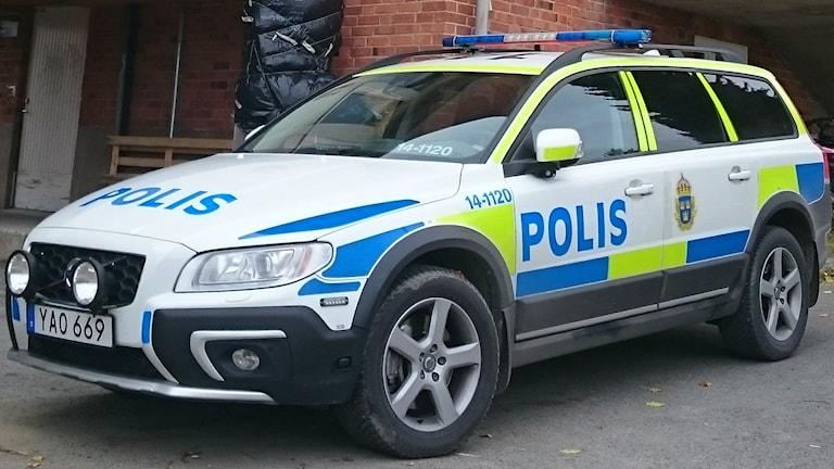 Polisbil parkerad framför byggnad med tefelfasad