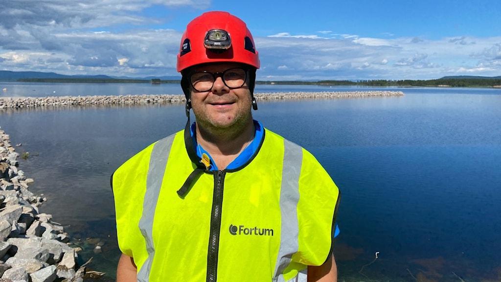 en man i röd hjälm, gul reflexväst och fyrkantiga glasögon framför en sjö i Sveg