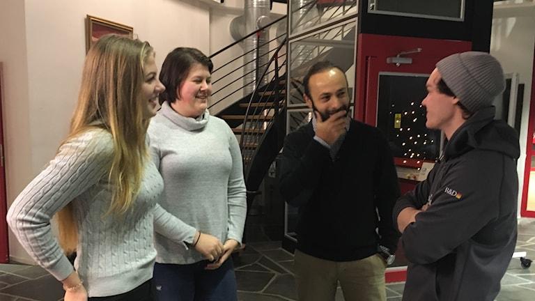 Tre elever, två blonda tjejer och en kille med grå mössa, och en mörkhårig lärare som står i radiohusets entre, de samtalar och ser glada ut.