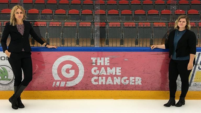 Två kvinnor står i en ishockeyrink vid en skylt med orden The Game Changer