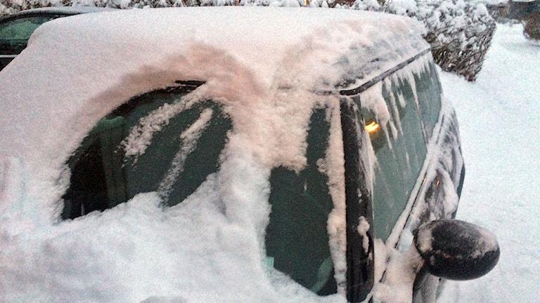 Bil med snö på taket och isiga rutor