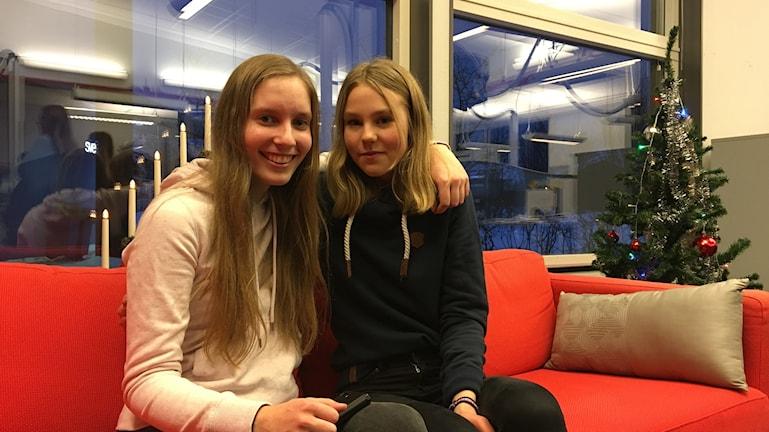 Två tjejer sitter bredvid varandra i soffa.
