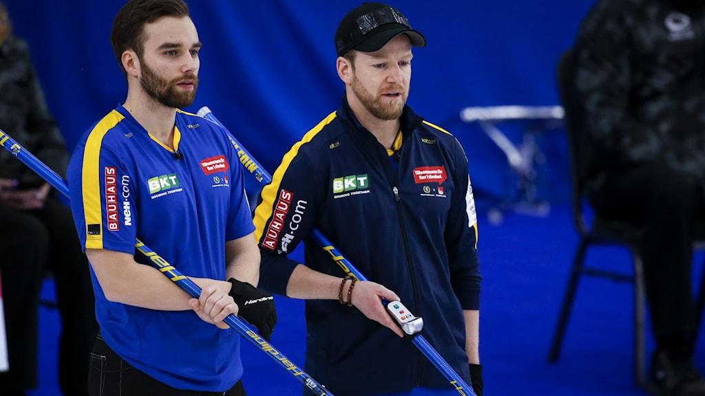 Två män i blågula kläder står och pratar. I bakgrunden syns ett blått skynke.