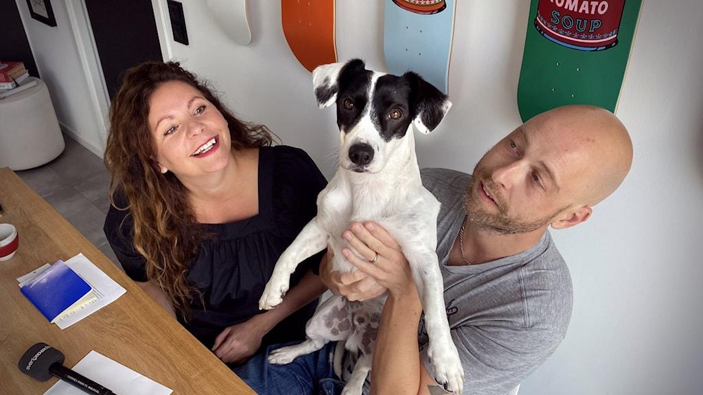Man och kvinna vid köksbord tillsammans med en hund.
