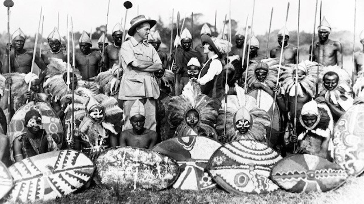 Herr och fru Martin Johnson med en grupp unga krigare ur Lumbwa-stammen, redo för jakt på en flock lejon som dödat deras boskap och några av stammens äldre medlemmar. 1920-tal, fotograf okänd. (SVT Bild)