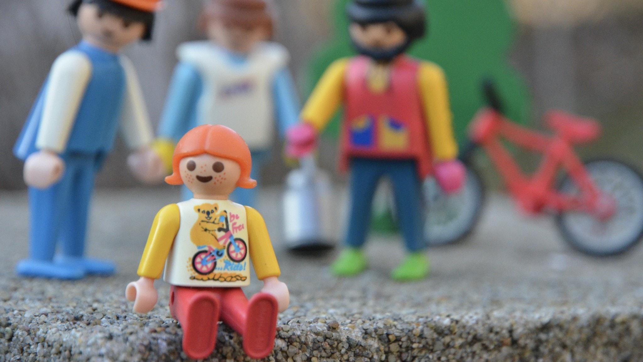 En barn-plastfigur med tre vuxen-plastfigurer som håller hand med varandra i bakgrunden.