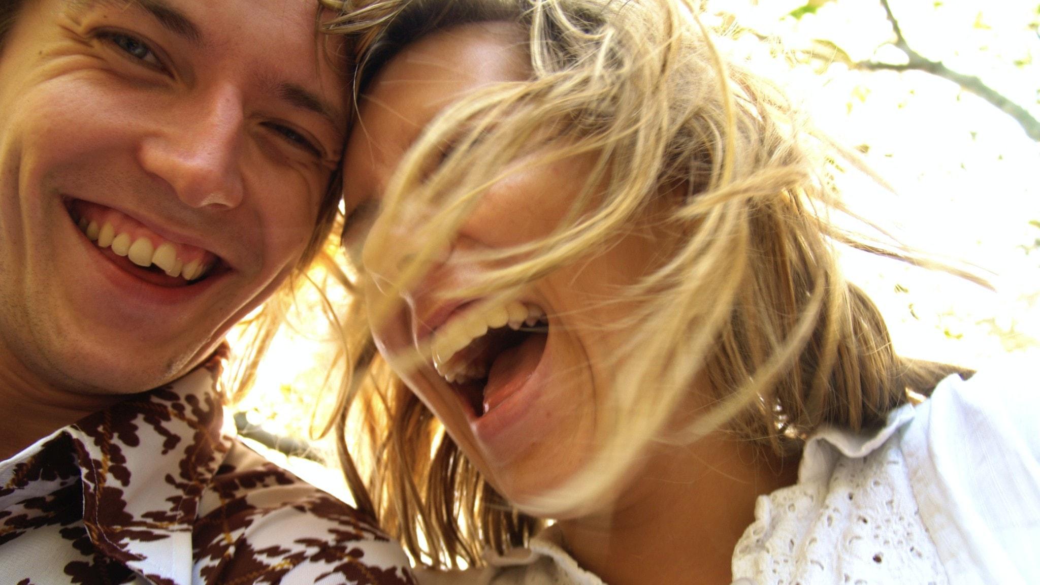 Man och kvinna som skrattar med huvudena ihop.