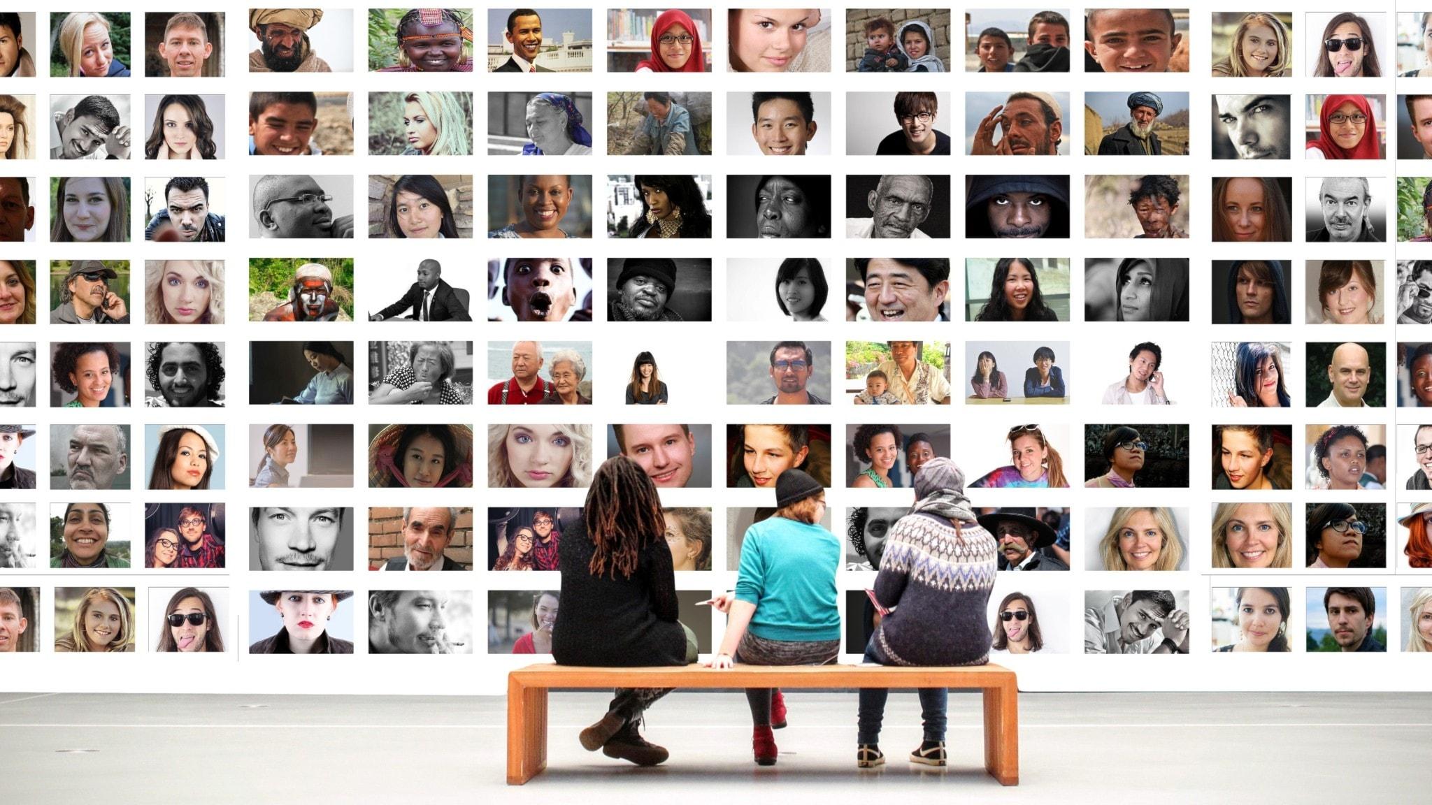 Tre personer sitter på en bänk och tittar på massor med fotografier med människor med olika urspurng.