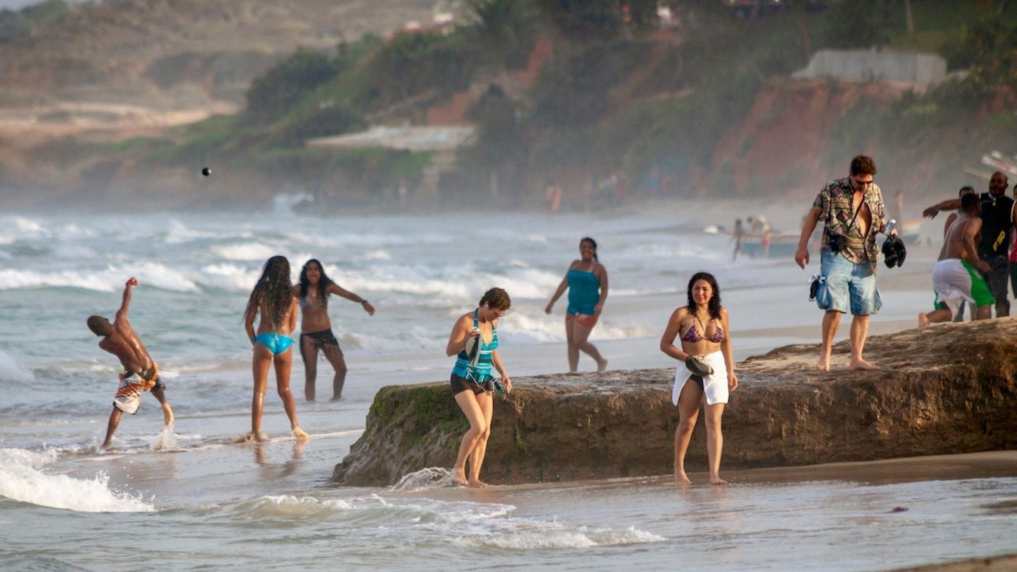 Människor som leker och promenerar på en strand.