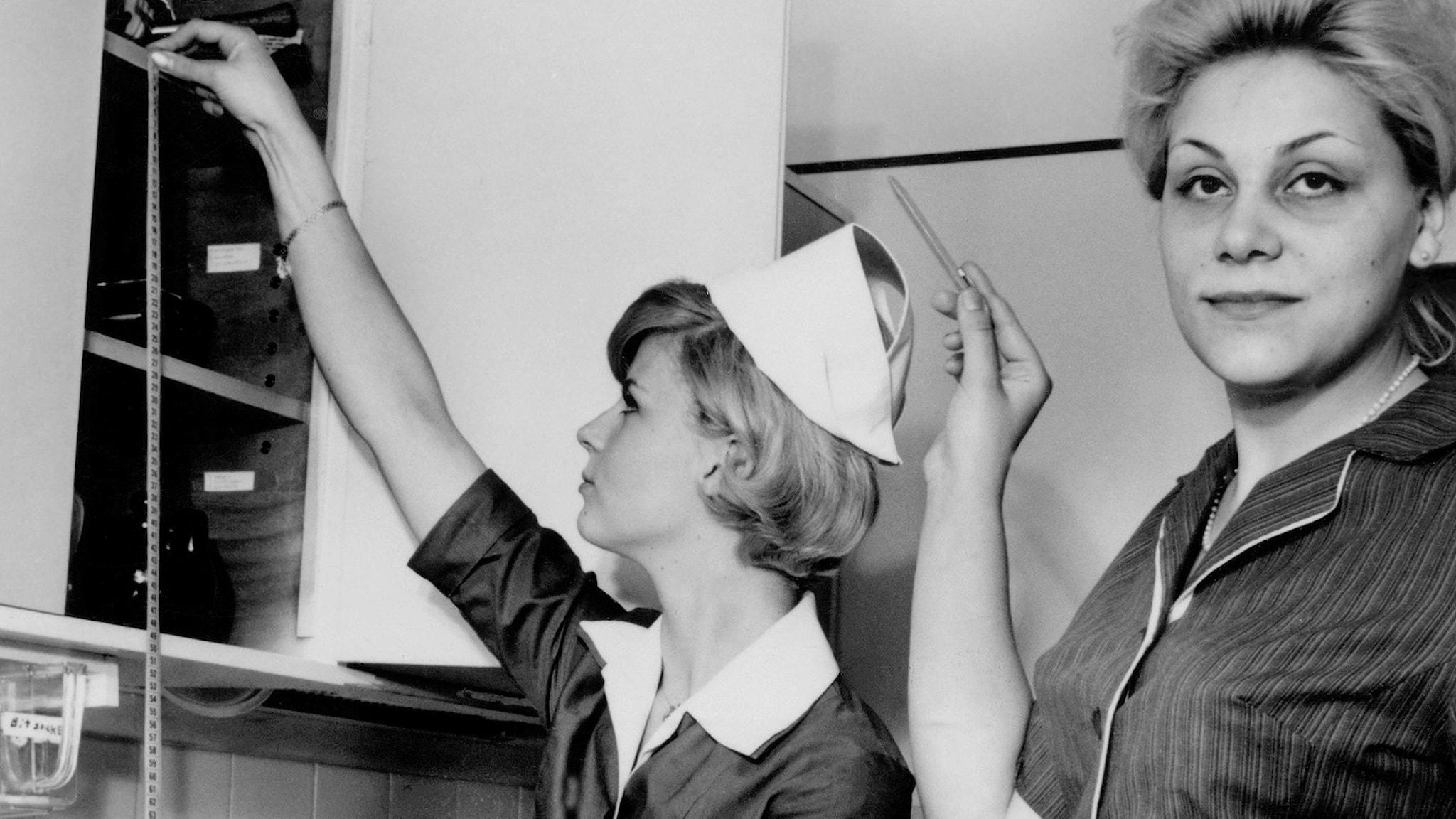Bild från Hemmens forskningsinstitut där två kvinnor mäter höjd på kökshyllor för bästa funktion och utrymme.