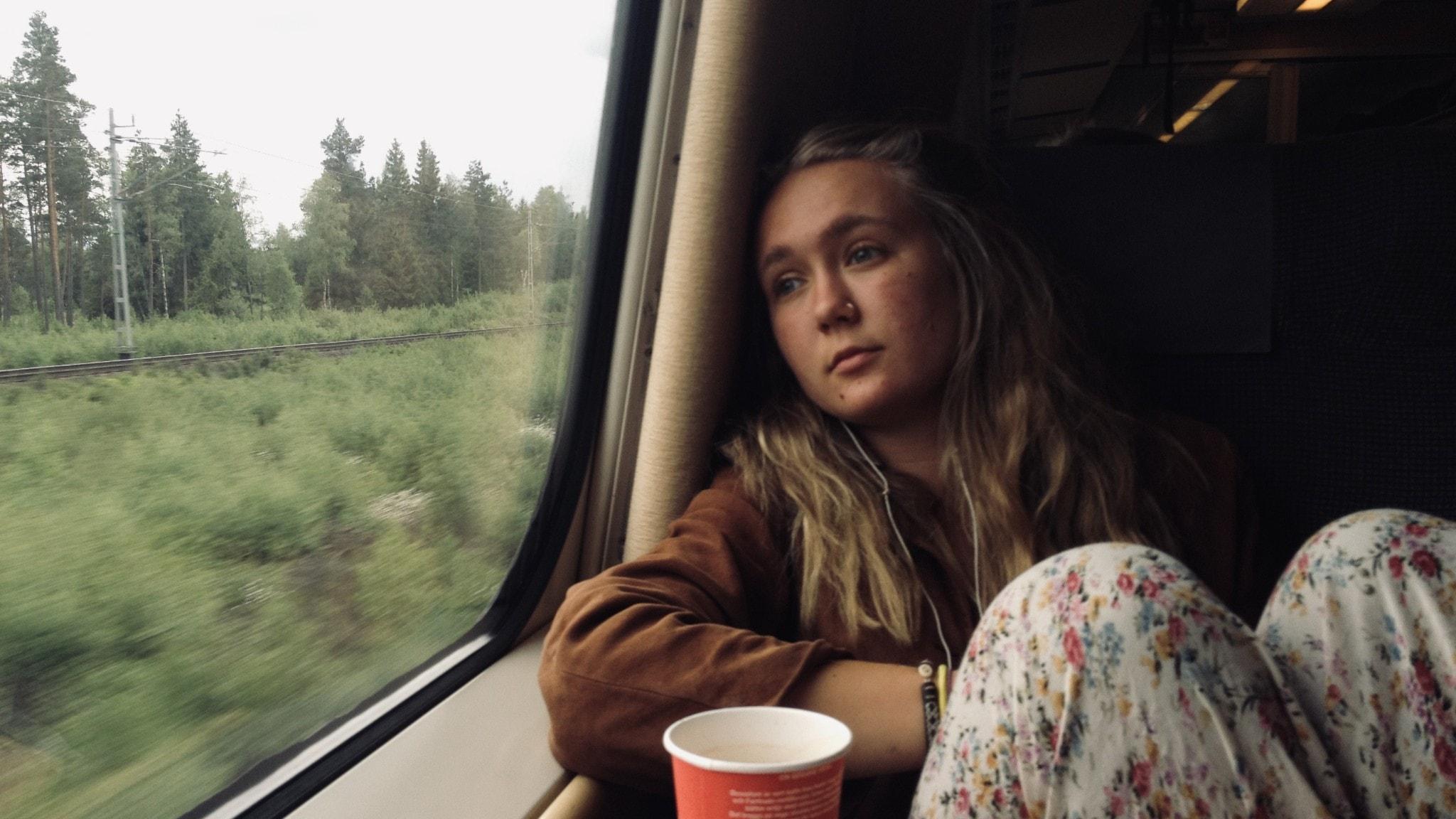 Ung kvinna tittar ut genom fönstret på ett tåg.