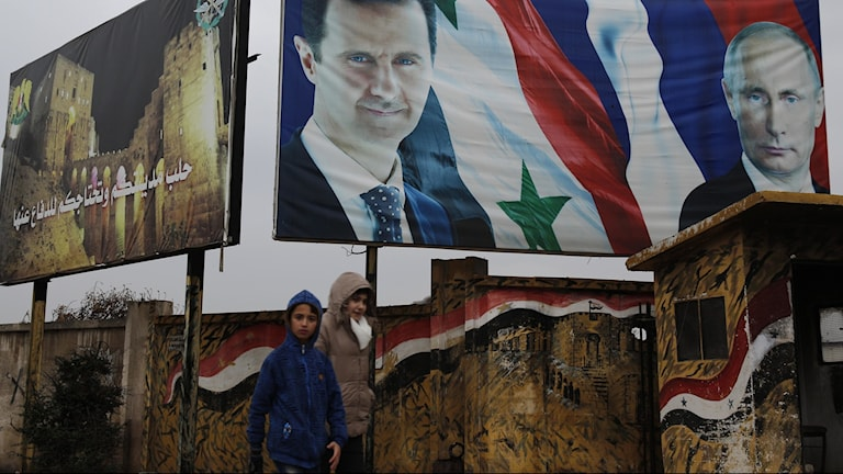 Syrian walk by posters of Syrian President Bashar Assad and Russian President Vladimir Putin in Aleppo, Syria