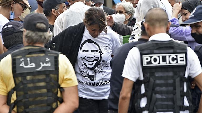 Algeriska säkerhetsstyrkor möter demonstranter utanför domstolen. Demonstranterna kräver journalistens frigivning.