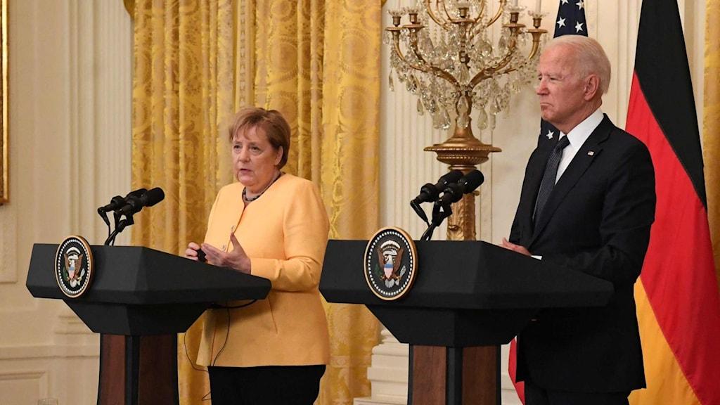 Man och kvinna framför amerikansk och tysk flagga.