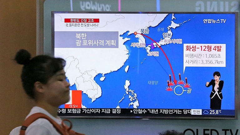 En kvinna går förbi en tv-skärm som visar en karta över östra Asien.