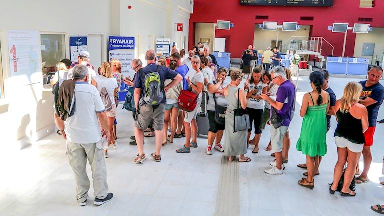 Resenärer köar vid informationshallen på Chania Airport på Kreta