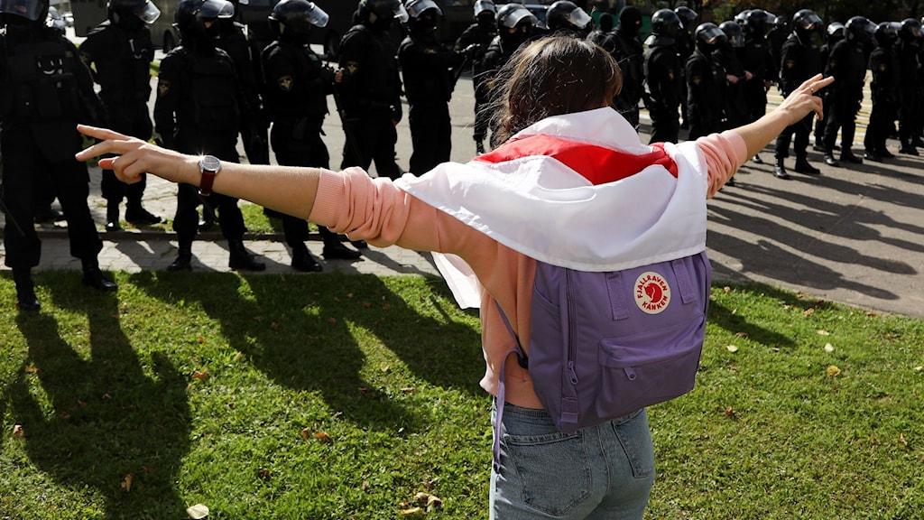 Person protesterar framför polisen, Minsk, Belarus.
