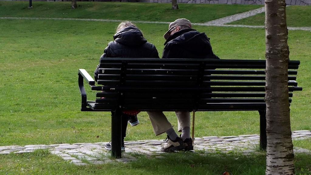 Två personer sittet på en bänk.
