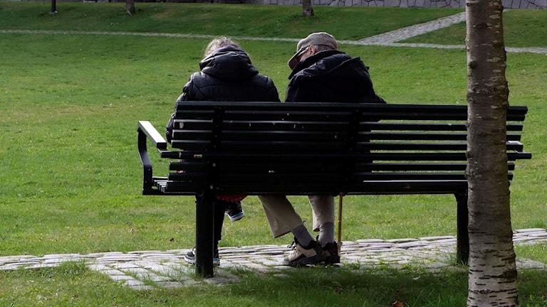 Två äldre personer sitter på en bänk.
