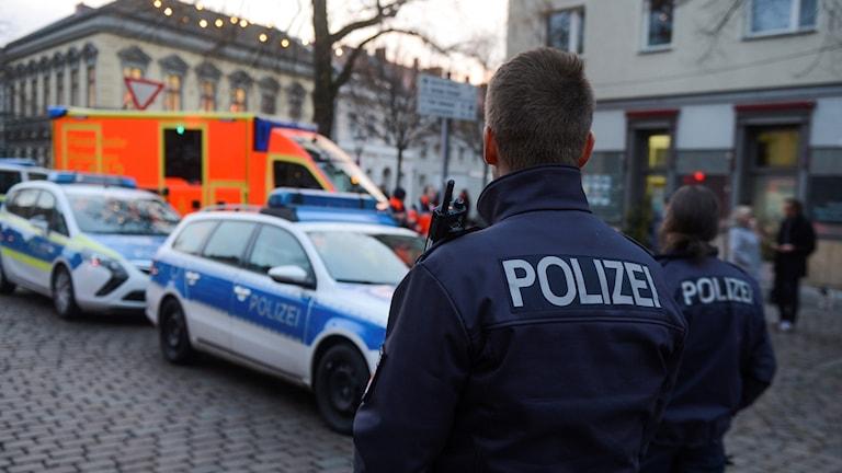 Poliser står framför utryckningsfordon