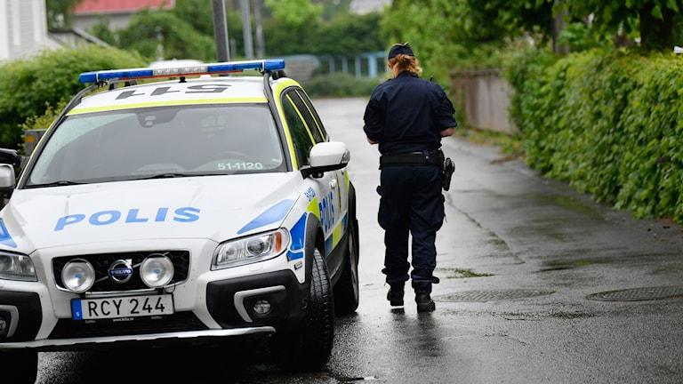 En polis intill en polisbil.