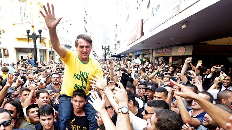 Man som sitter på en annan mans axlar i en folkmassa.