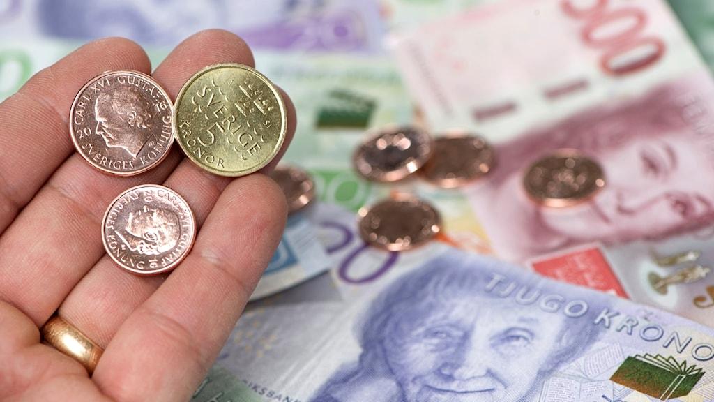 Mynt i en hand, sedlar i bakgrunden