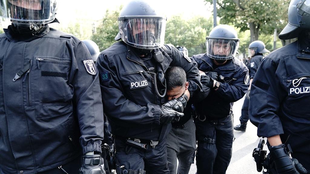 Tysk polis griper en man under gårdagens demonstrationer mot landets coronarestriktioner.