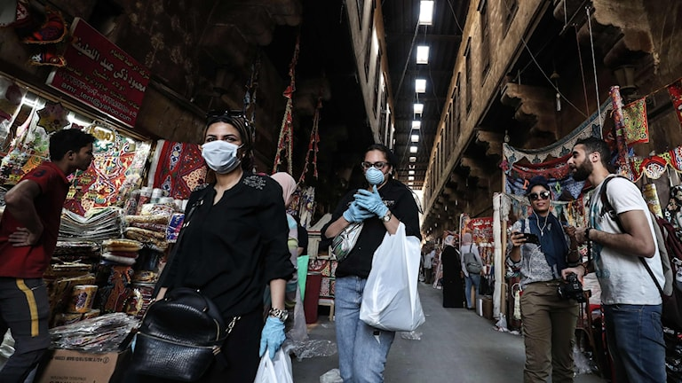 Kunder med och utan ansiktsskydd vid en butik i Kairo.