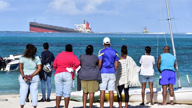 människor står på stranden och tittar på fartyget som gått på grund