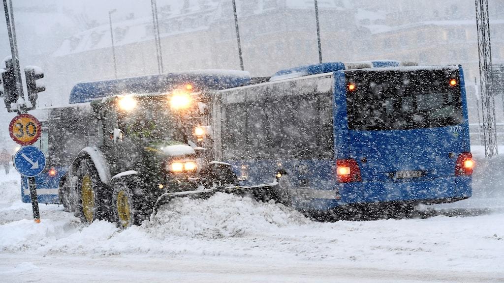 En plogbil plogar på en snöfylld gata vid Slussen i centrala Stockholm. Huvudstaden har bombarderats av snö under natten.