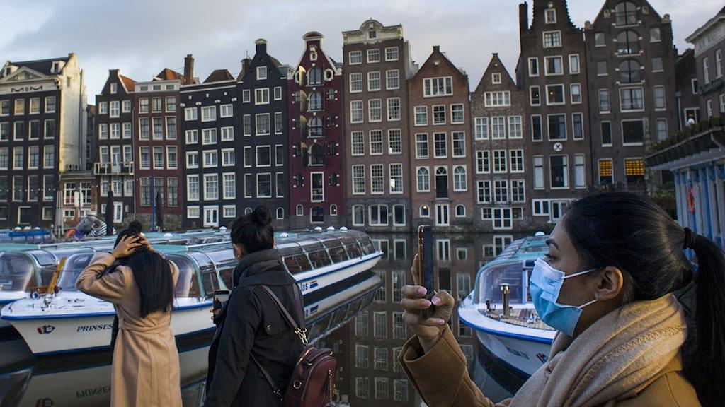 Människor med ansiktsmask vid kanalen i Amsterdam.