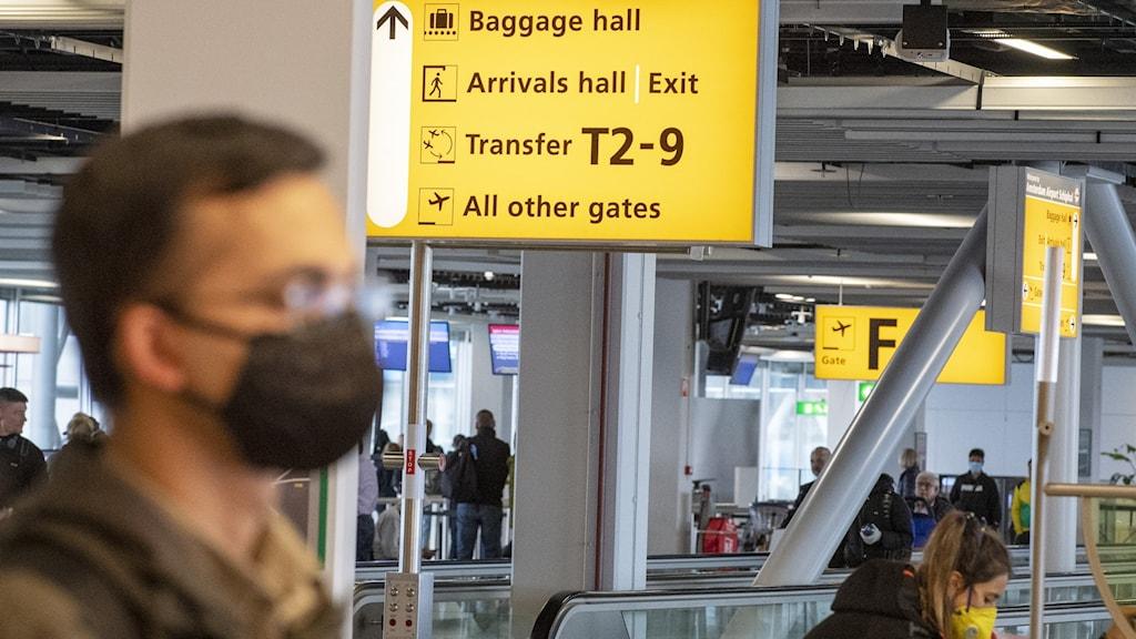 Resenärer på Amsterdams flygplats Schiphol använder munskydd på grund av rädsla för Coronavirus.
