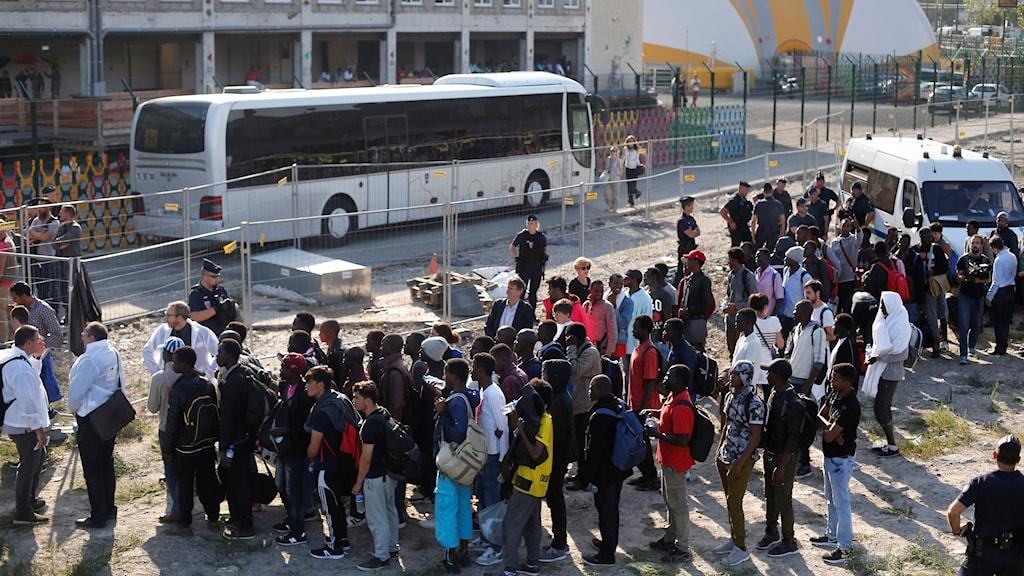 Migranter som väntar på en buss som ska evakuera dem från ett asylläger.