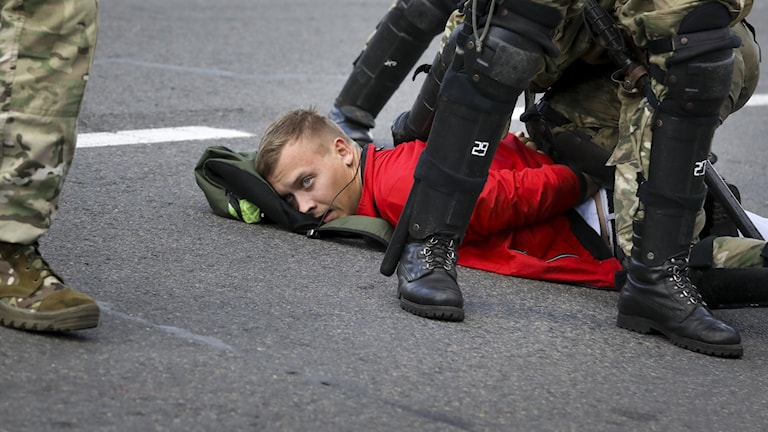 Demonstrant i Belarus omgiven av poliser