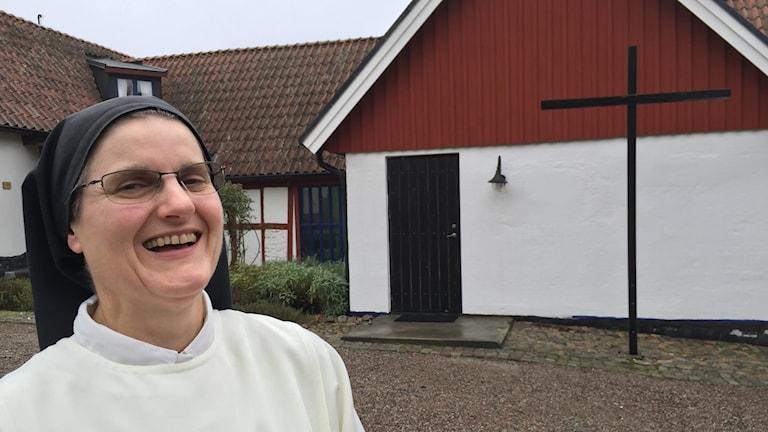Bilden visar syster Céline, föreståndare för Rögle kloster utanför Lund. Hon är klädd i domnikanersystrarnas vita dräkt och bär svart dok. Hon skrattar och i bakgrunden ser man en del av den gård i rött korsvirke som är klostret. Ett kors pryder en gavel. Foto: Anna Bubenko/Sveriges Radio.