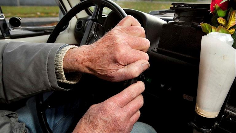 En äldre person håller i en bilratt.
