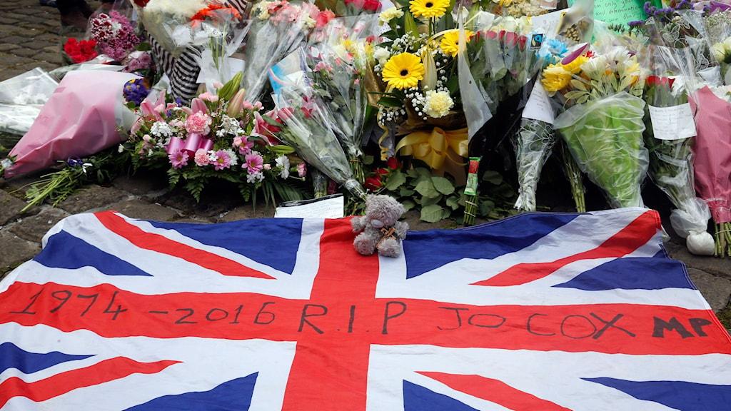 """Brittisk flagga med texten """"R.I.P. Jo Cox"""" och blombuketter."""