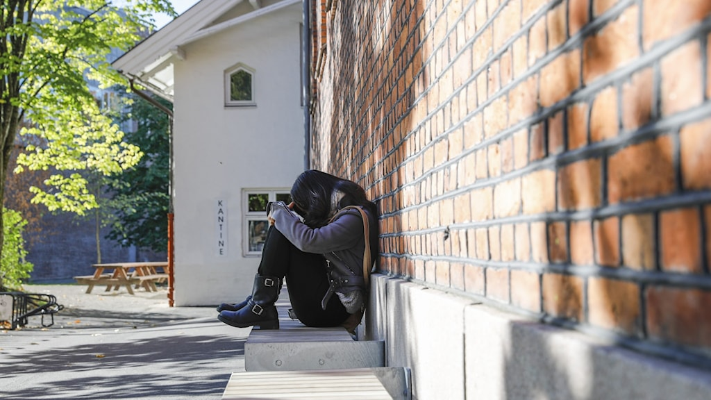 Ledsen tjej sitter längs en vägg med huvudet i händerna.