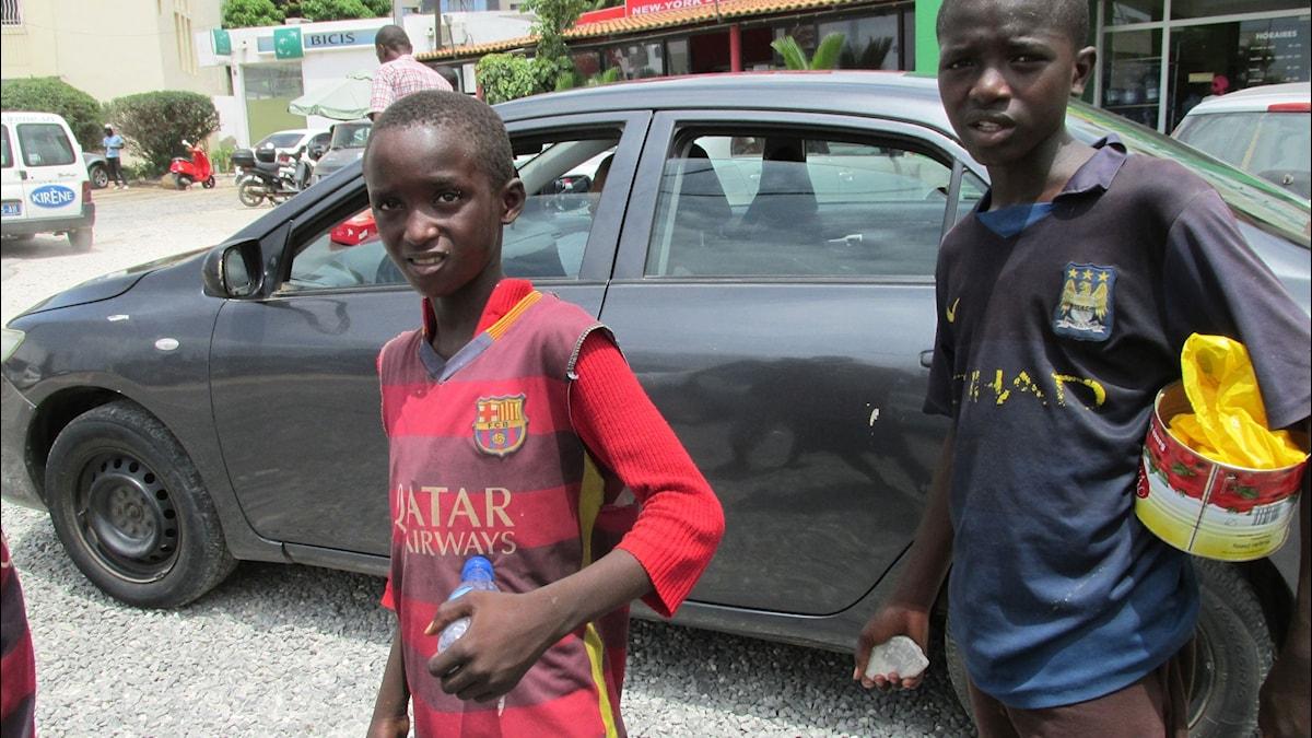 Två pojkar står på gatan i Senegal