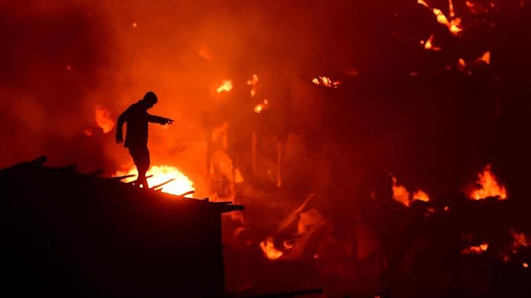 Bild på en människa som står på ett hustak i Dhaka där branden rasar.