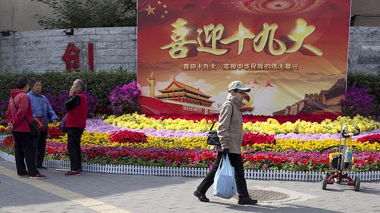 """""""Välkommen till den 19:e partikongressen"""", är budskapet på de färgglada banderollerna som pryder Pekings gator. Den kinesiska regeringen har vidtagit ett antal tunga säkerhetsåtgärder inför det politiska toppmötet.  Ng Han Guan/AP/TT ."""