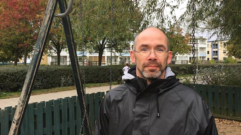 Bilden visar Sören Geist, som står vid en gungställning. I bakgrunden ser man huslängor. Foto: Anna Bubenko/Sveriges Radio.