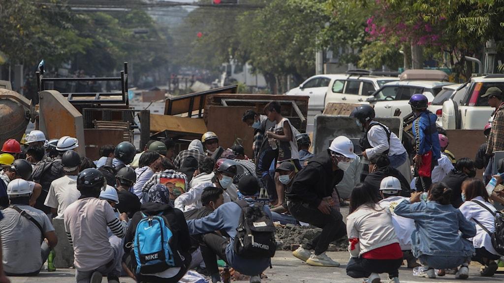Demonstranter som protesterar mot juntans kupp tar skydd bakom en barrikad.