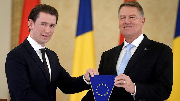 Österrikes förbundskansler skakar hand med Rumäniens president och håller i en EU-flagga.
