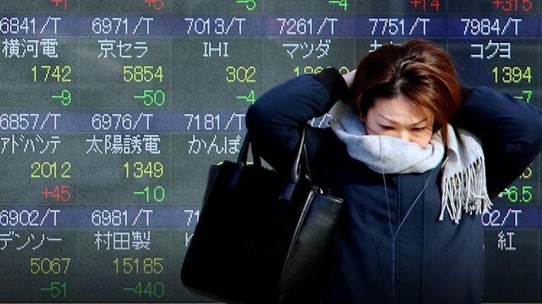 Kvinna rättar till en halsduk framför en skärm som visar siffror från Tokyobörsen