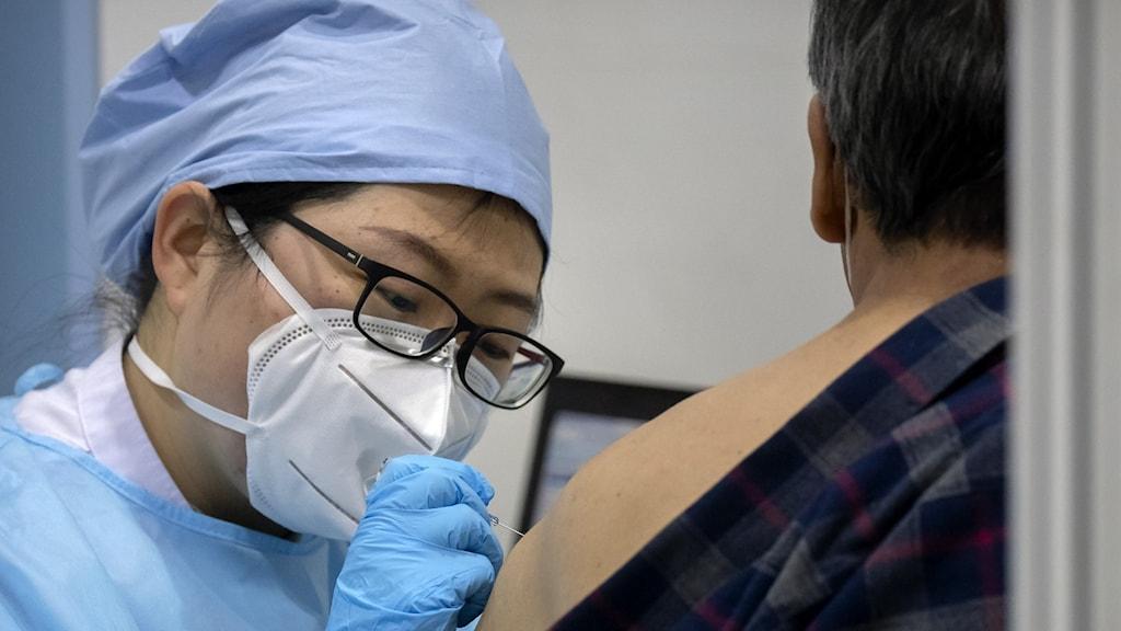 Person i munskydd ger en spruta i axeln.